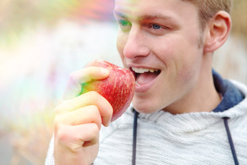 handsome man eating a red apple