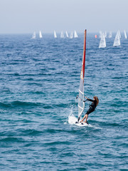 Young athlete in a black tracksuit exercising in windsurfing in the Mediterranean sea in Nahariya, Israel