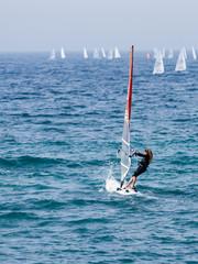 Young athlete in a black tracksuit exercising in windsurfing in the Mediterranean sea in Nahariya, Israel