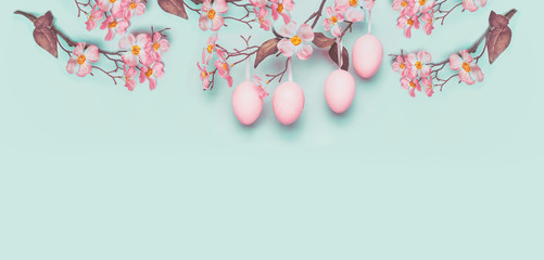 Easter banner with hanging pastel pink Easter eggs and spring blossom at light at blue turquoise...