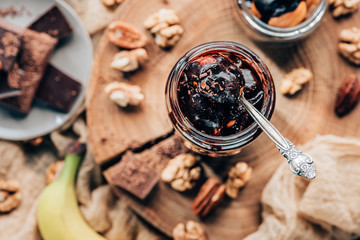 top view of sweet tasty chocolate dessert in glass jar with spoon