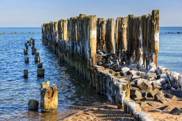 Frozen wooden breakwaters line at Baltic Sea, Babie Doly, Poland