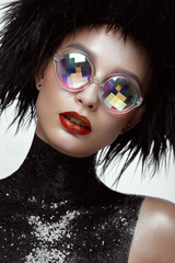 Beautiful fashion woman with creative make-up, wig and color glasses. The beauty of the face. Photos shot in the studio.