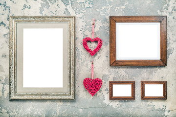 Wooden photo or picture frames blanks and pair of handmade Valentine's day love hearts hanging on vintage aged grunge textured concrete wall background. Retro old style filtered photo