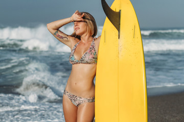 attractive blonde woman in bikini standing on beach with surf board