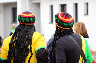 carnival, two men with jamaica caps and rasta wig, rear view