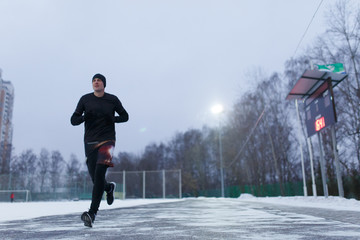 Image of running sporty man in stadium on background of trees