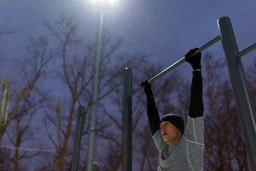 Image of athlete pulling up on bar in evening