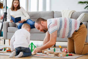 Family picture of father and son playing on floor in toy road with cars