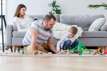 Image of happy parents with son playing toy road sitting on floor