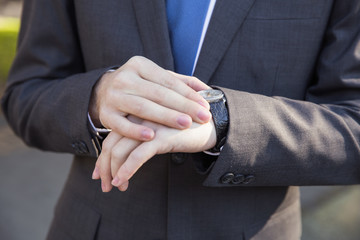 Man in business suit looking at his watch