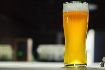 Tall glass of light beer in a brewery