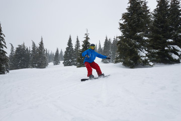 Snowboarder, wearing blue jacket, rides down a mountain slope