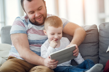 Photo of dad with his son with tablet sitting on gray sofa