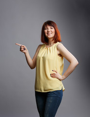Photo of young woman pointing finger at gray blank background