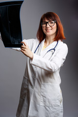 Picture of female doctor in glasses and white coat with looking at x-ray