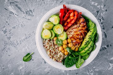 Vegetable bowl lunch with grilled chicken and quinoa, spinach, avocado, brussels sprouts, paprika and chickpea