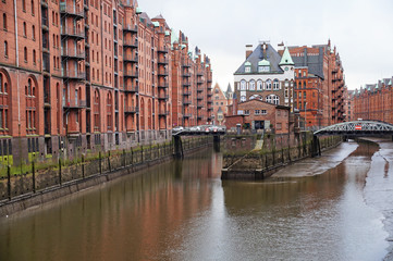 Speicherstadt. Port warehouse in Hamburg. Hamburg is a harsh German city. The urban landscape of northern Germany. View of city canals from the bridge.