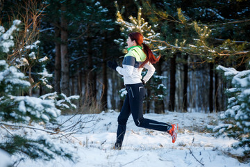 Picture of young woman sportswoman running through winter forest