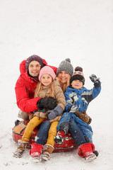 Picture of happy family with daughter and son sitting on tubing in winter
