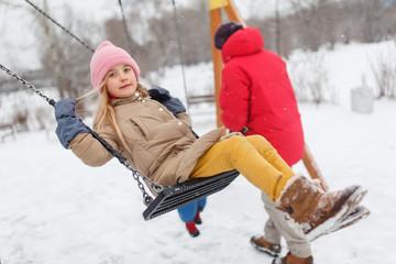 Photo of girl swinging in winter