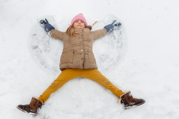 Image of girl lying on her back in snow at park