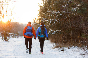 Romantic picture from back of man and woman with backpacks in winter