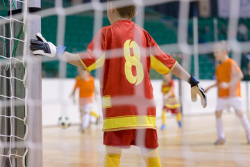 Football futsal training for children. Indoor football goalkeeper standing In goal. Indoor soccer young player with a soccer ball in a sports hall. Sport background.
