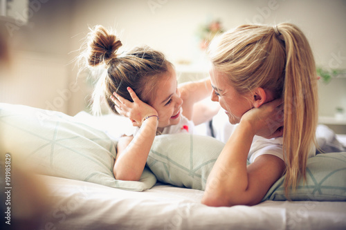 Mother and daughter lying on a bed looking etch other.