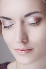 The girl's face with professional makeup on the eyes closed and clean skin close-up