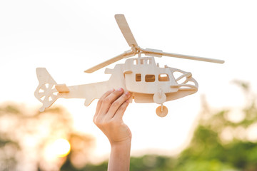 Hand holding helicopter wooden plane toy with sun set.