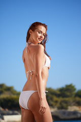 portrait of happy wet young woman in white bikini standing in sea water
