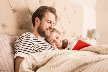 Father and daughter reading a book in a bed