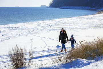 Mother with little son walking on snowy beach, Poland