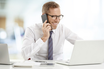 Businessman consulting on mobile phone with his client. Portrait of happy financial assistant business man using cell phone and making call while working on laptop at the office.