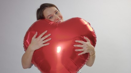 caucasian woman hugs a huge red heart and hold it joying