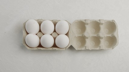 woman's hand open an eggbox with white eggs ant take off oneof them