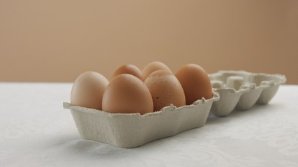 box with brown eggs in studio on white table