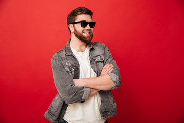Image of fashion young man wearing sunglasses and denim smiling and posing with hands folded, isolated over red background