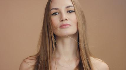 woman's portrait in studio in beige tones. blonde woman with long straight hair