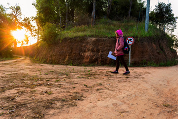 Countryside student young girl walking on mountain trail at morning time.