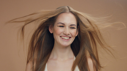 beauty woman model in studio on beige background with wind in hair bllowing it lauging a lot