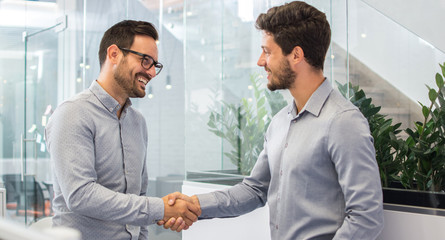 Two smiling businessmen shaking hands together while standing in modern office.