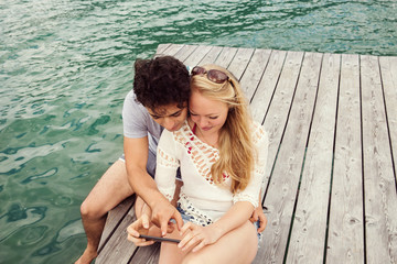 Couple sitting on pier looking at smartphone