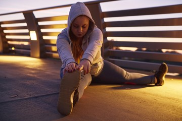 Curvaceous young woman training, touching toes on footbridge