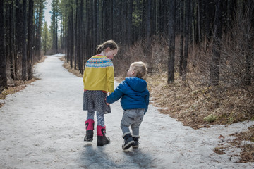 Sister and brother walking on road in forest