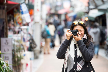 Woman taking pictures with mirrorless digital camera in street, Tokyo
