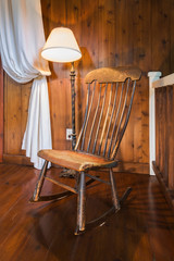 Antique wooden rocking chair and lamp, inside a New Hampton style home, Quebec, Canada