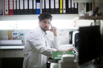 Portrait of young male pharmacist at desk using computer in pharmacy