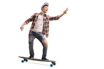 Teenage hipster riding a longboard and making a peace sign